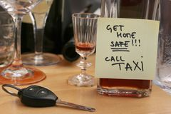 Don't drink and drive concept. Car keys on the table full of empty glasses, bottles at party, don't drink and drive concept, post it note for taxi Royalty Free Stock Photos