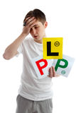 Don't fail driving test examination. Teenage boy holding L and P plate driving licence signs for car and looking forlorn. He may need to take more expert driving royalty free stock photo