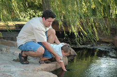Don't fall in. Father and son on the bank of a creek. Father sharing the world with his son stock images