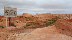 Don't Fall in the Opal Diggings. Characteristic signs around Coober Pedy warning travelers not to walk backwards lest one fall into one of the millions of Opal Royalty Free Stock Photography