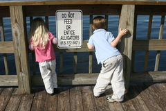 Don't Feed the Alligators. Florida photo of 2 kids and Don't feed the gators sign Royalty Free Stock Photo