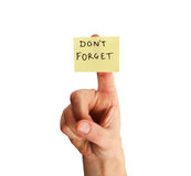 Don't forget note on finger. Yellow sticky note saying don't forget on a woman's finger isolated on white background Stock Photo