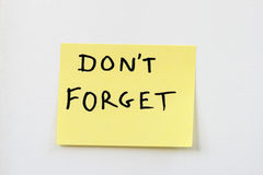 Don't forget on yellow sticky note. Don't forget on a small yellow sticky note stuck on a white wall Royalty Free Stock Images
