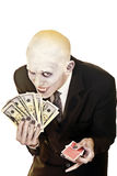 Don't gamble unless you know the facts. Vampire inviting public  to gamble with cash in one hand and playing cards in other Royalty Free Stock Image