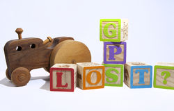 Don't get lost!. Wooden toy blocks spelling GPS and Lost with a wooden handmade toy car or truck Royalty Free Stock Images