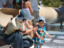 Don't get too wet sweetie. Mother and a baby girl having fun in a water park Stock Photography