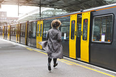 Don't go without me!. Rear view of a woman running to catch the train before it leaves the station without her Royalty Free Stock Image