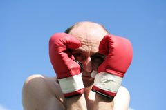 Don't hit me. Man wearing boxing gloves to protect him with a beautiful blue sky behind him stock photography