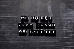 We don`t just teach we inspire on wooden blocks. Education, Motivation and inspiration concept royalty free illustration
