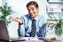 Don`t know what to do. Office worker spread his hands. Photo of young man working in the office. Business concept royalty free stock images