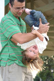 Don't Let Go!. Little girl laughing as her father playfully turns her upside-down stock image