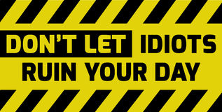 Don`t let idiots ruin your day sign. Yellow with stripes, road sign variation. Bright vivid sign with warning message Royalty Free Stock Photo
