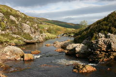 Don't let the sun fool you. Icy cold water makes its way down Dundonnel River to Little Loch Broom Stock Image