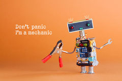 Don`t panic I`m a mechanic concept. Toy robot handyman with pliers ready for service work. Fun character colorful head Royalty Free Stock Photos
