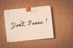 Don't Panic. Note pin on bulletin board Stock Images
