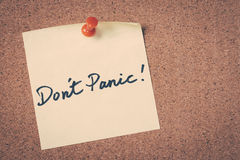 Don't Panic. Note pin on bulletin board Royalty Free Stock Photo