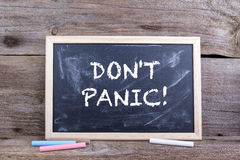 DON'T PANIC! Text on blackboard.  Stock Photos