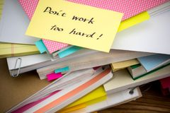 Don ` t praca Zbyt Mocno; Stos Biznesowi dokumenty na biurku Zdjęcie Stock