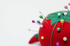 Half of a pin cushion and needles - a tomato. A vintage tomato pin cushion stock photography