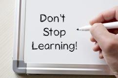 Don't stop learning written on whiteboard. Human hand writing don't stop learning on whiteboard Stock Photo