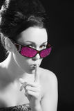 Don't tell anyone. Cute brunette with pink sunglasses putting her finger to her lips Stock Photo