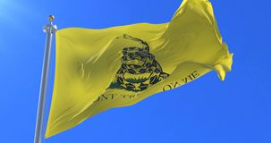 Don`t Tread On Me Gadsden Flag waving at wind in slow with blue sky, loop. Ed stock footage
