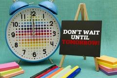 DON`T WAIT UNTIL TOMORROW. Message written on a small blackboard Stock Photos