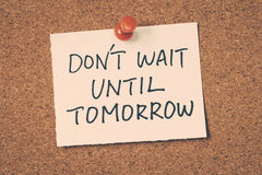 Don't wait until tomorrow. Note pin on the bulletin board Stock Photo