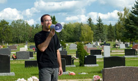 Don't Wake Up The Dead. Concept image of the saying, Don't wake up the dead, featuring a young man talking into a megaphone and standing in a graveyard Stock Photo