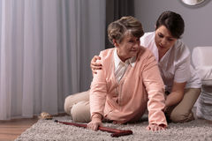 Don't worry, i'll help you to stand up. Carer helping senior women with walking stick to stand up from floor Stock Photos