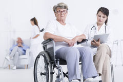 Don't worry, we will take care of you. Cropped shot of a sad female patient in a wheelchair next to her doctor Royalty Free Stock Photo