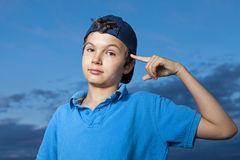 Don't you get it?. Teenage boy, standing outside, its evening, pointing a finger to his head Royalty Free Stock Photography