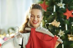 Dona de casa à moda de sorriso que seleciona o equipamento festivo do Natal foto de stock