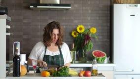 A dona de casa atrativa nova prepara um jantar romântico na cozinha Interior moderno brilhante da cozinha, dia do ` s da mãe filme