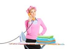 Dona de casa bonita com posição dos rolos e do telefone do cabelo Imagens de Stock Royalty Free