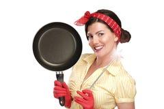 Dona de casa bonita nova da mulher que mostra uma varinha mágica em pratos Fotos de Stock