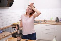 Dona de casa cansado que inclina-se no robô de cozinha ao cozinhar na cozinha em casa Receita complicada imagens de stock