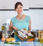 Dona de casa com fatias de peixes do merluccius foto de stock royalty free