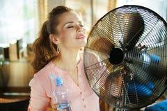 Dona de casa com a garrafa fria da água usando o fã imagem de stock royalty free