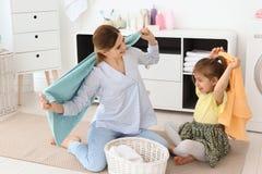 Dona de casa com sua filha que tem o divertimento ao dobrar toalhas recentemente lavadas na lavandaria fotografia de stock royalty free