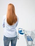 Dona de casa com um carrinho de compras que faz uma escolha imagens de stock