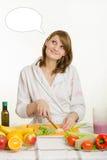 A dona de casa corta vegetais para a salada e olhares sonhadores em uma nuvem sobre seus pensamentos principais Imagem de Stock