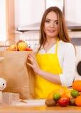 Dona de casa da mulher na cozinha com muitos frutos Imagens de Stock Royalty Free