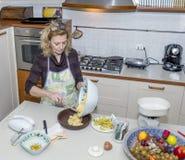 A dona de casa derrama a massa no molde para preparar um bolo em uma cozinha desarrumado imagens de stock royalty free
