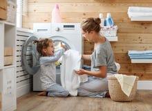 Dona de casa e criança felizes da mãe da família na lavanderia com washin foto de stock royalty free