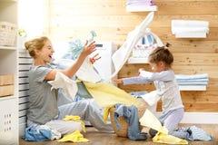 Dona de casa e criança felizes da mãe da família na lavanderia com washin fotografia de stock royalty free