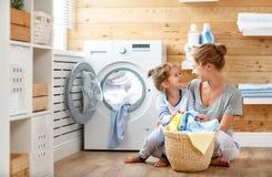 Dona de casa e criança felizes da mãe da família na lavanderia com washin fotos de stock royalty free