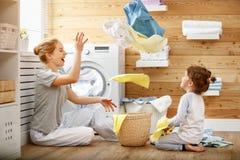 Dona de casa e criança felizes da mãe da família na lavanderia com washin foto de stock