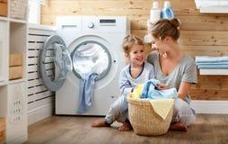 Dona de casa e criança felizes da mãe da família na lavanderia com washin fotografia de stock