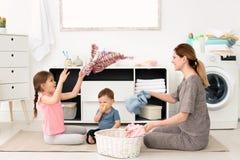 Dona de casa e crianças que têm o divertimento ao dobrar-se recentemente imagem de stock